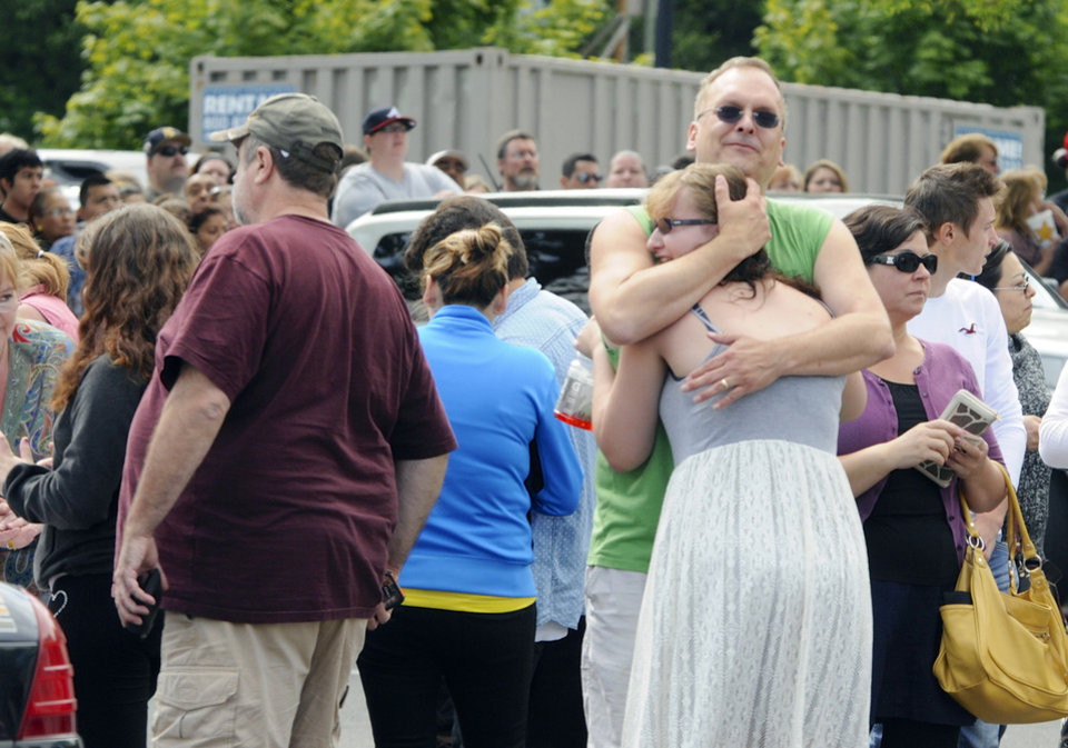 Photo - A family embraces as students arrived at the Fred Meyer grocery store parking lot in Wood Village, Ore., after a shooting at Reynolds High School Tuesday, June 10, 2014, in nearby Troutdale. A gunman killed a student at the high school east of Portland Tuesday and the shooter is also dead, police said. (AP Photo/Greg Wahl-Stephens)