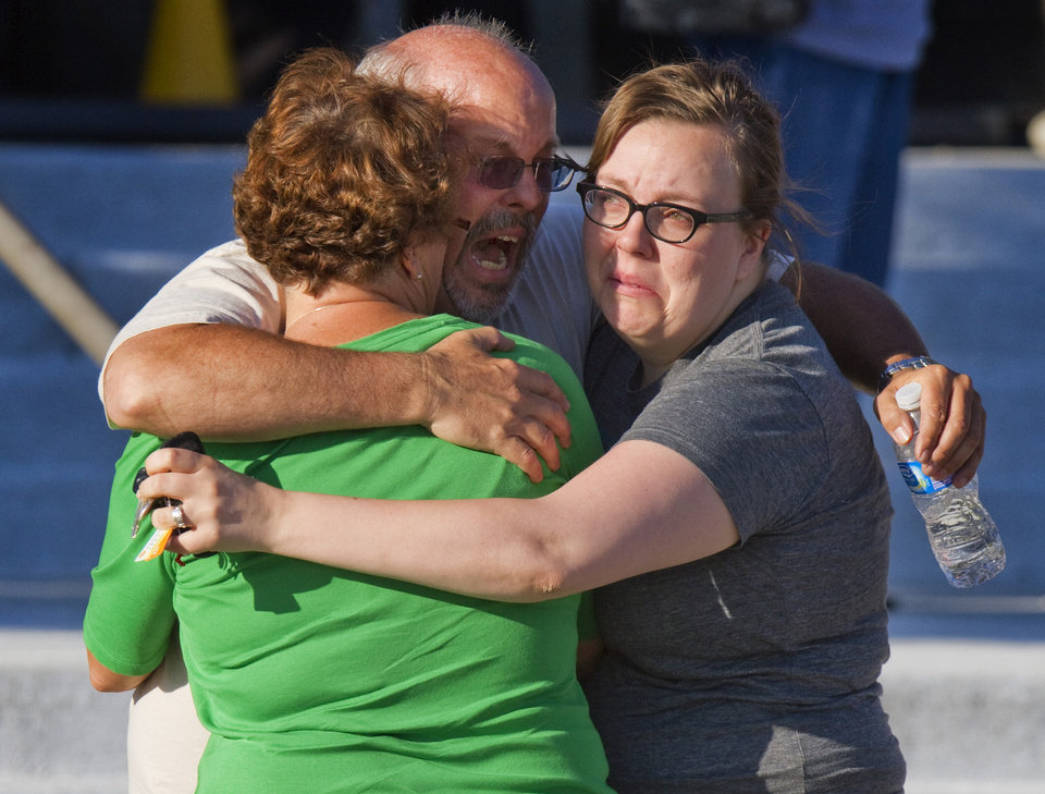 FILE - In this Friday, July 20, 2012 file photo, Tom Sullivan, center, embraces family members outside Gateway High School where he had been searching for his son Alex Sullivan who was killed when a gunman opened fire, in Aurora, Colo. Sullivan says he'll be present at the reopening of the move theater where the shooting occurred even though his daughter-in-law and relatives of some other victims are refusing to go. (AP Photo/Barry Gutierrez, File)