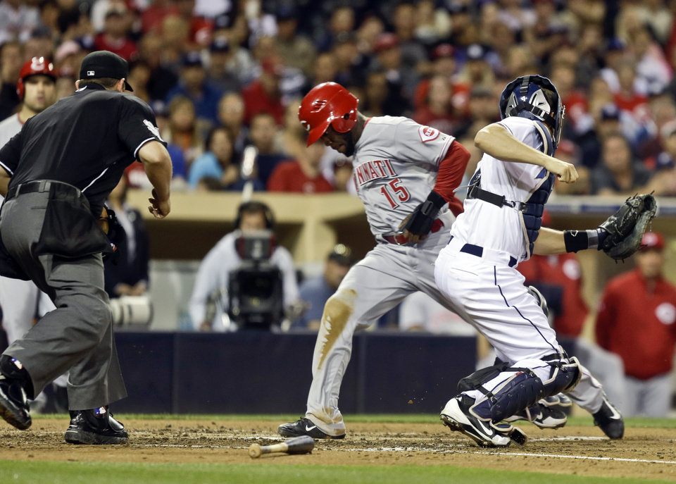 Photo - Cincinnati Reds' Derrick Robinson beats the throw and the tag by San Diego Padres catcher Nick Hundley while scoring from third on an infield ground ball in the fifth inning of a baseball game in San Diego, Monday, July 29, 2013. The umpire is Brian Knight.  (AP Photo/Lenny Ignelzi)