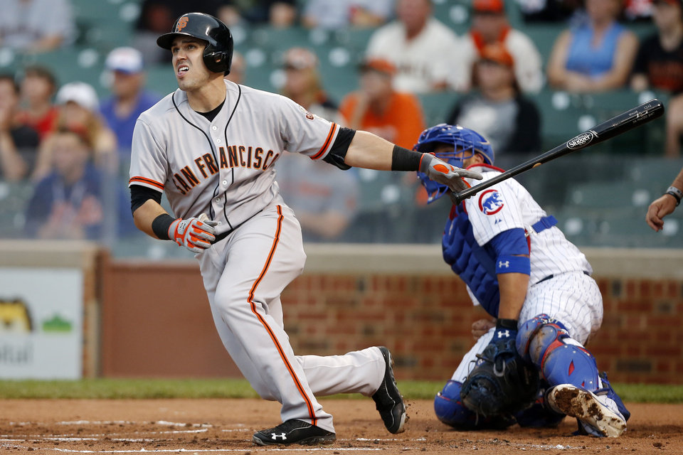 Photo - San Francisco Giants' Adam Duvall, left, hits a double against the Chicago Cubs during the sixth inning of the continuation of a baseball game that began Tuesday, on Thursday, Aug. 21, 2014, in Chicago. Tuesday's game was suspended in the fifth inning due to rain. (AP Photo/Andrew A. Nelles)