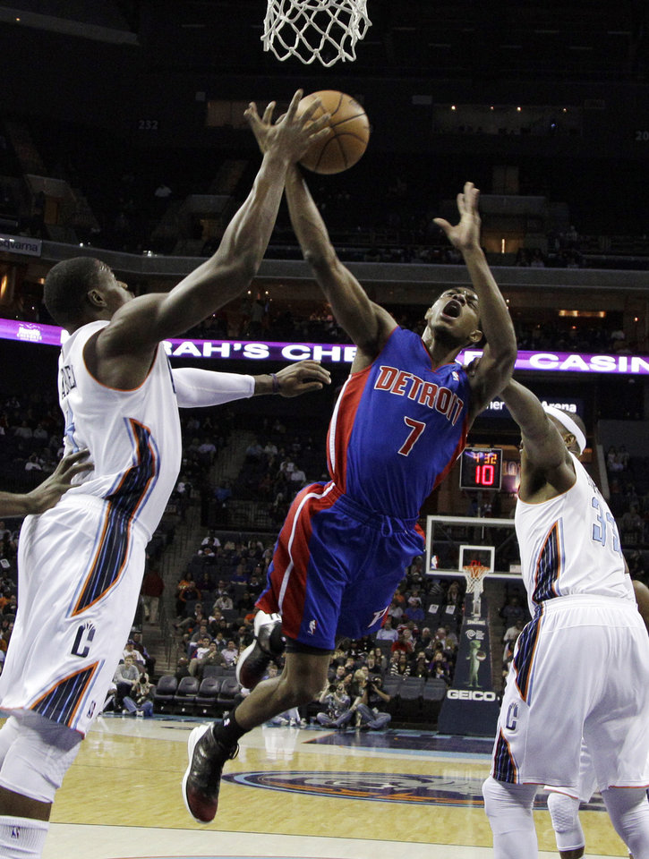 Detroit Pistons' Brandon Knight (7) is fouled as he drives between Charlotte Bobcats' Brendan Haywood, right, and Michael Kidd-Gilchrist during the first half of an NBA basketball game in Charlotte, N.C., Wednesday, Feb. 20, 2013. (AP Photo/Chuck Burton)