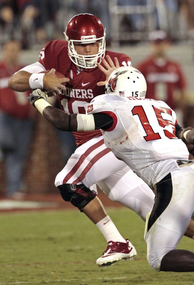 Oklahoma Sooners' Blake Bell (10) stiff arms Ball State Cardinals' Aaron Morris (15) on a keeper during the second half of the college football game in which the University of Oklahoma Sooners (OU) defeated the Ball State Cardinals 62-6 at Gaylord Family-Oklahoma Memorial Stadium on Saturday, Oct. 1, 2011, in Norman, Okla. Photo by Steve Sisney, The Oklahoman