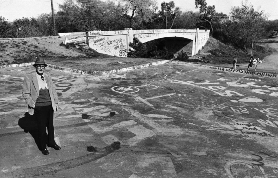 Photo -  Lowell Moseley looks over the graffiti-ridden parking lot.  Staff photo by Bob Albright.  Photo dated 11/12/1984