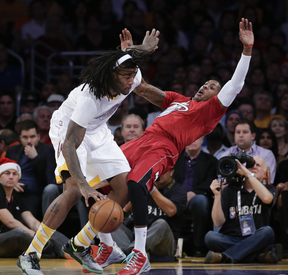 Photo - Los Angeles Lakers center Jordan Hill, left, pushes Miami Heat guard Dwyane Wade during the second half of an NBA basketball game in Los Angeles, Wednesday, Dec. 25, 2013. Hill received an offensive foul on the play. (AP Photo/Chris Carlson)