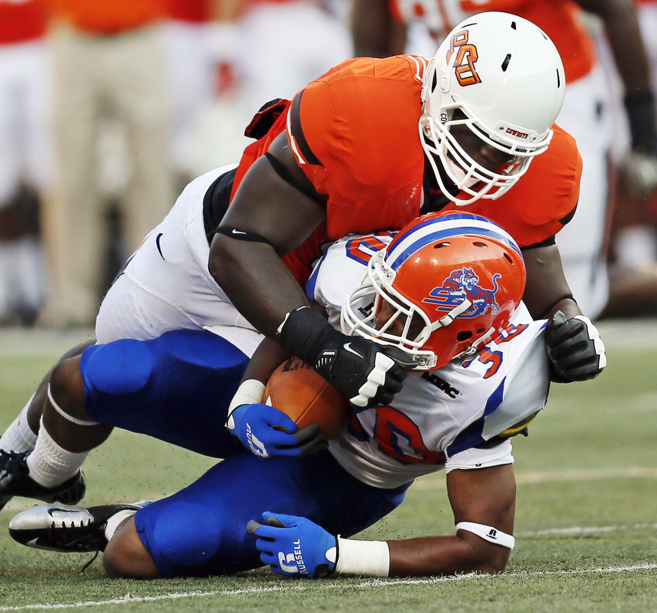 OSU\'s Calvin Barnett (99) brings down Lereginald Veals (30) of Savannah State during a college football game between Oklahoma State University (OSU) and Savannah State University at Boone Pickens Stadium in Stillwater, Okla., Saturday, Sept. 1, 2012. Photo by Nate Billings, The Oklahoman