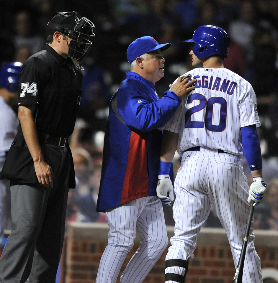 Photo - Chicago Cubs' Justin Ruggiano (20) is held back by Cubs manager Rick Renteria center, while home plate umpire John Tumpane (74) watches after Ruggiano struck out during the eighth inning of a baseball game against the Pittsburgh Pirates in Chicago, Saturday, June 21, 2014. (AP Photo/Paul Beaty)