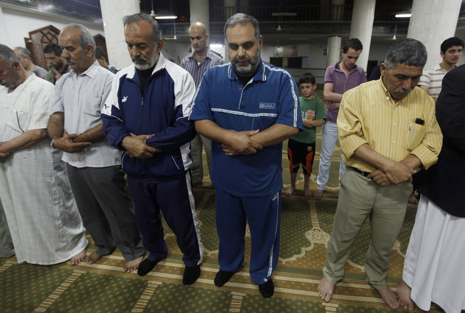 Photo - In this Monday, June 24, 2013 photo, Mohammed Rantisi, 55, offers the Fajr, the first of the five daily prayers, at a mosque in Gaza City. On the day of his induction, Baraa, Mohammed's son, was told to wait near a mosque. A white car drove up. Secret passwords were exchanged. And then he was sworn into the Muslim Brotherhood, an exclusive movement that sees itself on a divine mission to establish Islamic rule. AP reporters got rare access to the Rantisi family, the closest thing to a royal clan in the Brotherhood in Gaza, at a time when the movement is under siege throughout the region. (AP Photo/Hatem Moussa)