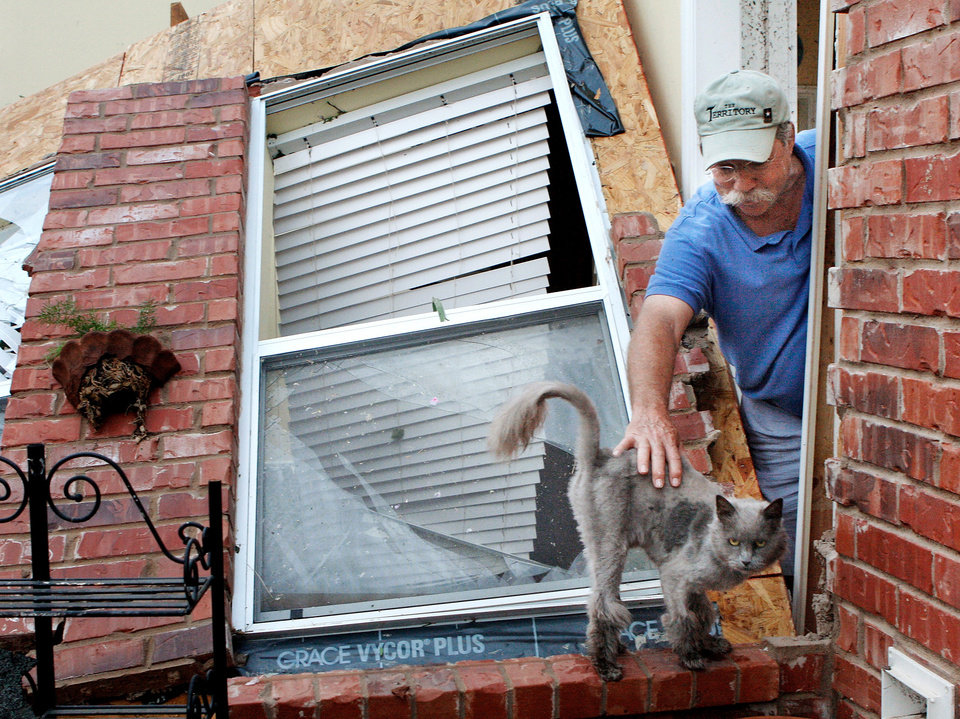 Photo - Johnny Hannah reaches through his kitchen doorway for Murphey, one of his family's cats who had wandered back to Hannah's home on the Cedar Valley East Golf Course after a tornado came through the area Tuesday afternoon,  May 24, 2011,   Johnny and his wife , Beth, were in the storm shelter when the tornado hit. Photo by Jim Beckel, The Oklahoman