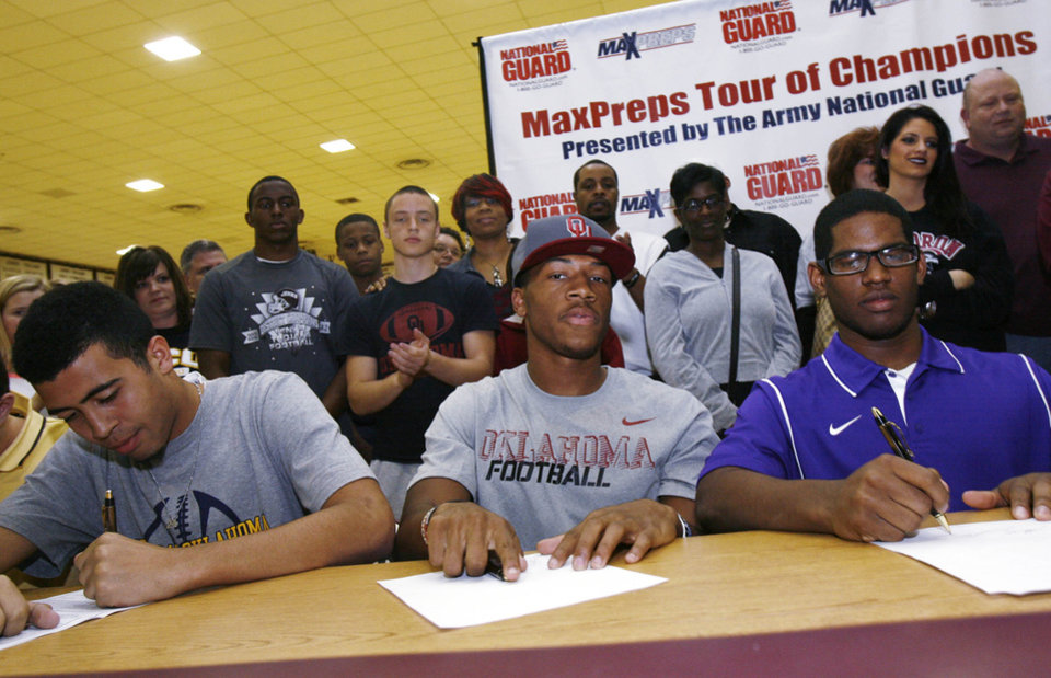 Photo - Members of the Jenks high school football team including Taylor Hunter (left), Jordan Smallwood, and Jeff Scallion sign up for their new college teams, taken during signing Day in Jenks, Okla., on February 6,2013. JAMES GIBBARD/Tulsa World