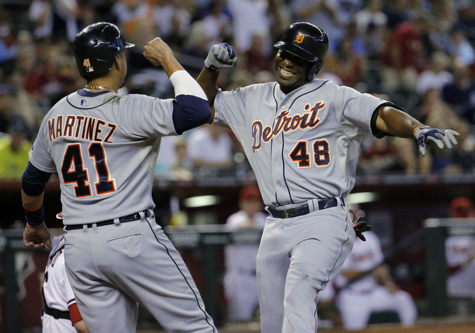 Photo - Detroit Tigers' Torii Hunter (48) celebrate his two run home run against the Arizona Diamondbacks with teammate Victor Martinez (41) during the first inning of a baseball game, Monday, July 21, 2014, in Phoenix.  (AP Photo/Matt York)
