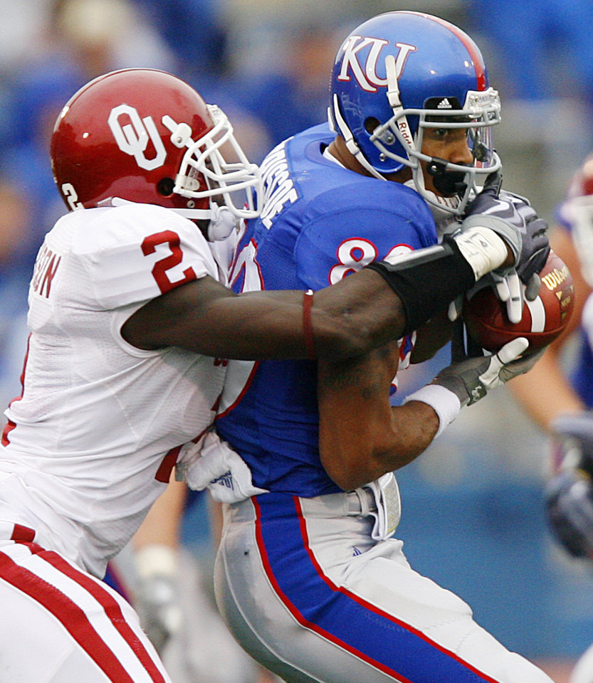Photo - Oklahoma's Brian Jackson (2) stops Kansas' Dezmon Briscoe (80) after a reception during the second half of the college football game between the University of Oklahoma Sooners (OU) and the University of Kansas Jayhawks (KU) on Saturday, Oct. 24, 2009, in Lawrence, Kan. Oklahoma won the game 35-13. Photo by Chris Landsberger, The Oklahoman