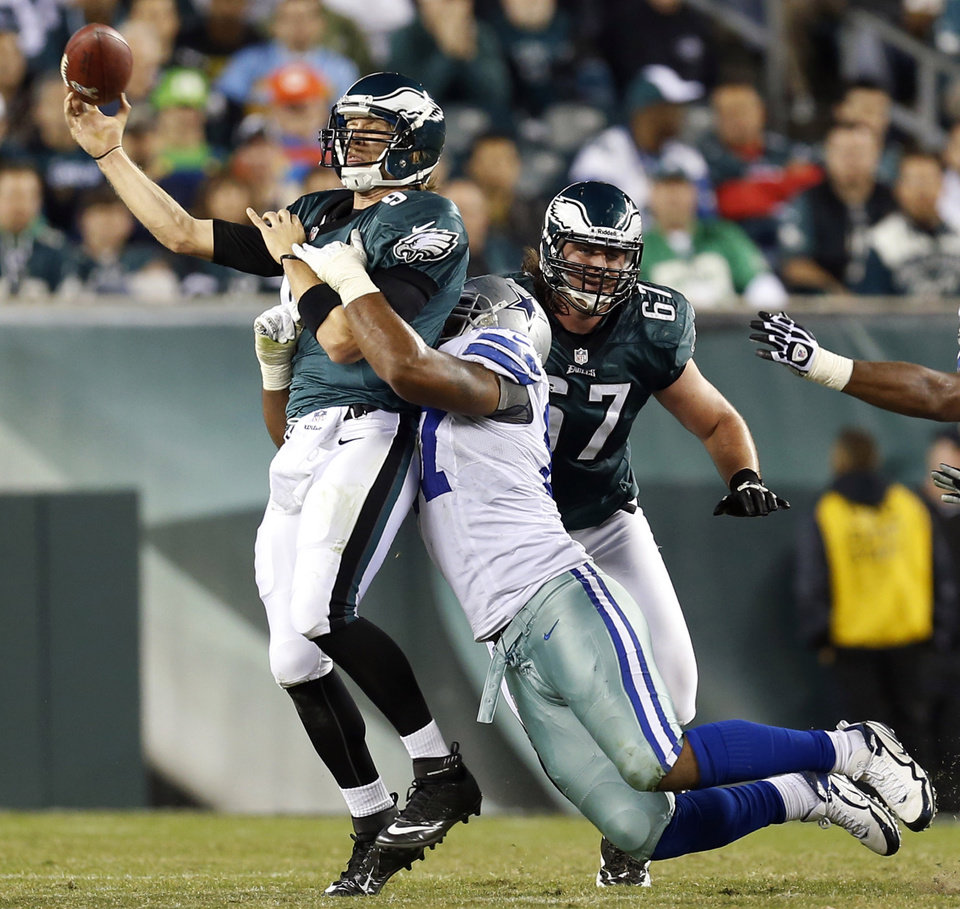 Philadelphia Eagles quarterback Nick Foles, left, is hit by Dallas Cowboys' Jason Hatcher as he throws in the second half of an NFL football game, Sunday, Nov. 11, 2012, in Philadelphia. (AP Photo/Julio Cortez)