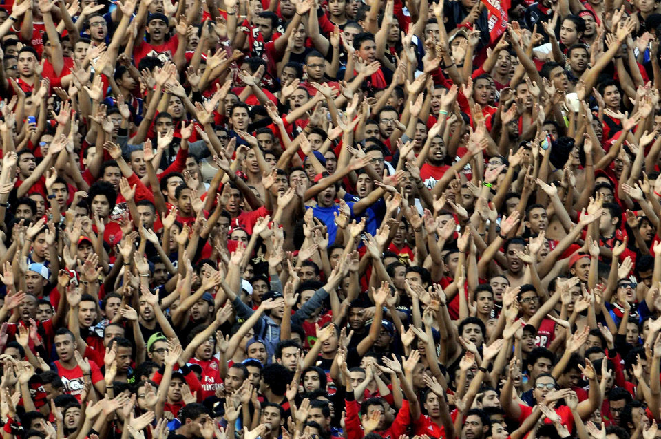 Photo - Egyptian club Al Ahly fans cheer during the African Champions League second leg final match between Egyptian Al Ahly club and South Africa's Orlando Pirates, at the Arab Contractors stadium in Cairo, Egypt, Sunday, Nov. 10, 2013. Hundreds of Egyptian soccer fans have clashed with police outside a Cairo stadium before the African Champions League final. (AP Photo/Osama Abdel Naby)