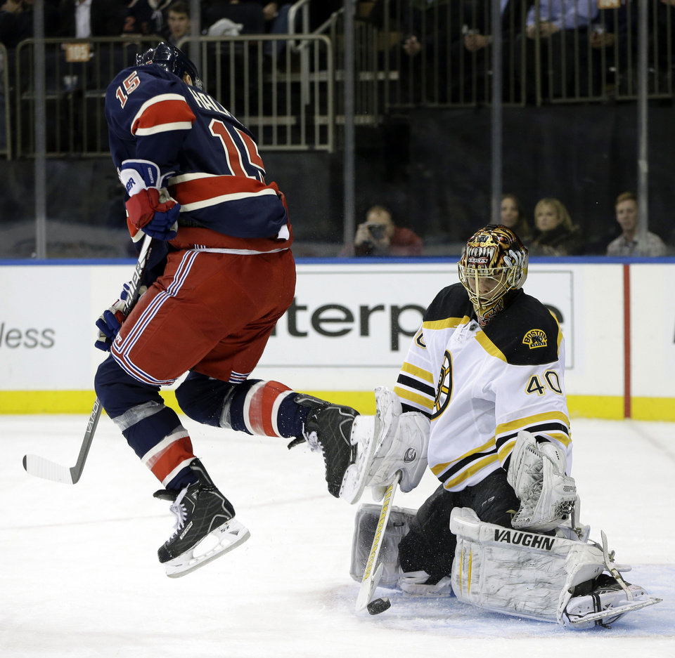 Photo - New York Rangers center Jeff Halpern (15) leaps to allow the puck through as Boston Bruins goalie Tuukka Rask (40) makes a save in the second period of their NHL hockey game at Madison Square Garden in New York, Wednesday, Jan. 23, 2013.  (AP Photo/Kathy Willens)