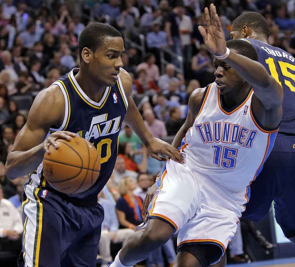 Photo - Oklahoma City Thunder's Reggie Jackson (15) defends on Utah Jazz's Alec Burks (10) during the NBA basketball game between the Oklahoma City Thunder and the Utah Jazz at Chesapeake Energy Arena on Wednesday, March 13, 2013, in Oklahoma City, Okla. Photo by Chris Landsberger, The Oklahoman
