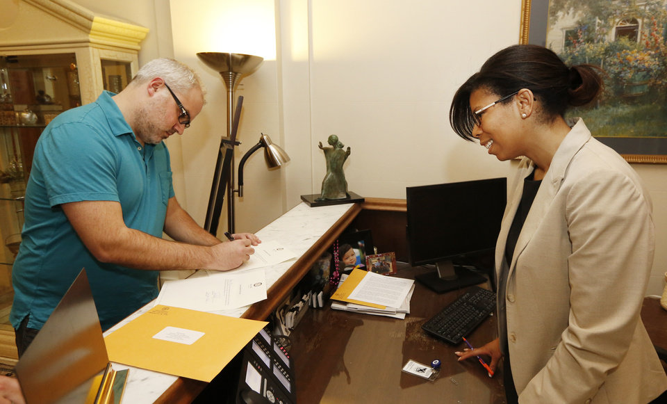 Rebecca Frazier, right, has Patrick Riley, publisher of The Lost Ogle sign for a copy of a computer disk released by Governor Mary Fallin\'s office that contains more than 50,000 pages of public records and information about how state officials made health care decisions at the State Capitol in Oklahoma City , Friday March 28, 2013. Photo By Steve Gooch, The Oklahoman