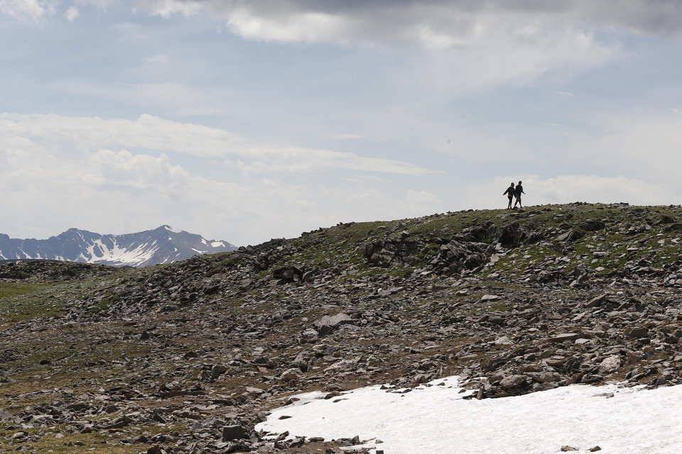 Photo - A couple walks together past a snowfield just off Trail Ridge Road, above tree-line at Rocky Mountain National Park, west of Estes Park, Colo., Monday, July 14, 2014. Lightning killed two people last weekend just miles apart in the popular park, where summer storms can close in quickly with deadly results. (AP Photo/Brennan Linsley)