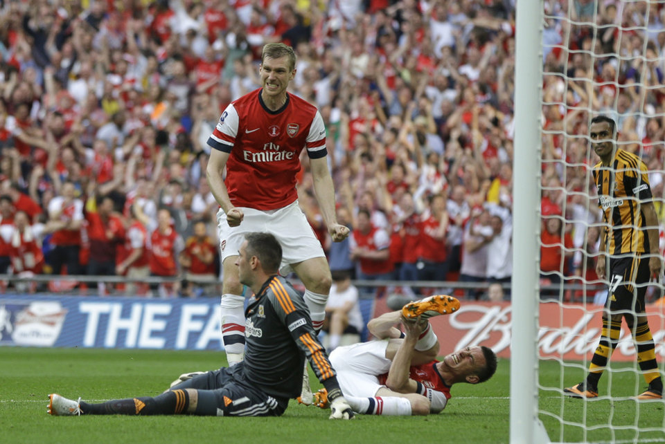 Photo - Arsenal's Laurent Koscielny, bottom right,  holds his leg after taking a knock when scoring his sides second goal during the English FA Cup final soccer match between Arsenal and Hull City at Wembley Stadium in London, Saturday, May 17, 2014. (AP Photo/Kirsty Wigglesworth)