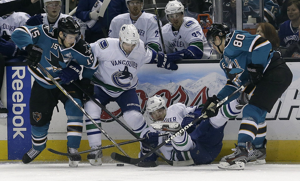 Photo - Vancouver Canucks right wing Jannik Hansen, from Denmark, bottom, looks for the puck in between defenseman Dan Hamhuis (2), San Jose Sharks center James Sheppard (15) and defenseman Matt Tennyson (80) during the second period of an NHL hockey game in San Jose, Calif., Monday, April 1, 2013. (AP Photo/Jeff Chiu)