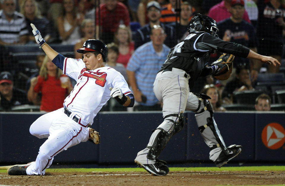 Photo - Atlanta Braves' Ramiro Pena, left, scores past Colorado Rockies catcher Jordan Pacheco on hit by Gerald Laird to break a 2-2 tie during the eighth inning of a baseball game Friday, May 23, 2014, in Atlanta. (AP Photo/David Tulis)