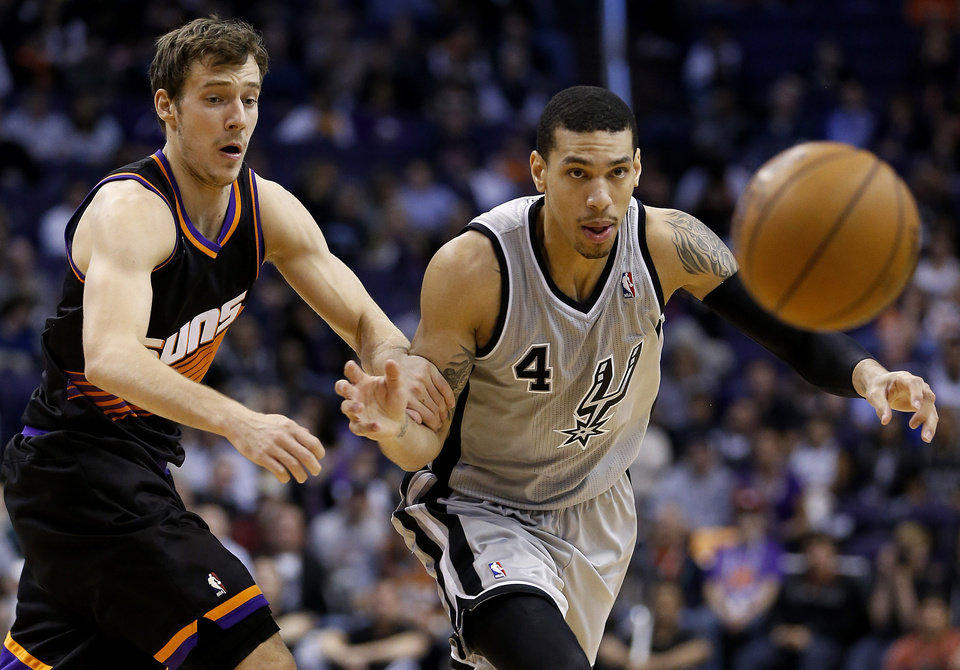 San Antonio Spurs' Danny Green (4) and Phoenix Suns' Goran Dragic, of Slovenia, chase the loose ball during the first half of an NBA basketball game, Sunday, Feb. 24, 2013, in Phoenix. (AP Photo/Matt York)