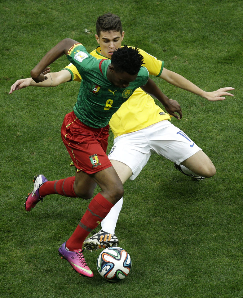 Photo - Brazil's Oscar fights for the ball with Cameroon's Benjamin Moukandjo during the group A World Cup soccer match between Cameroon and Brazil at the Estadio Nacional in Brasilia, Brazil, Monday, June 23, 2014. (AP Photo/Christophe Ena)
