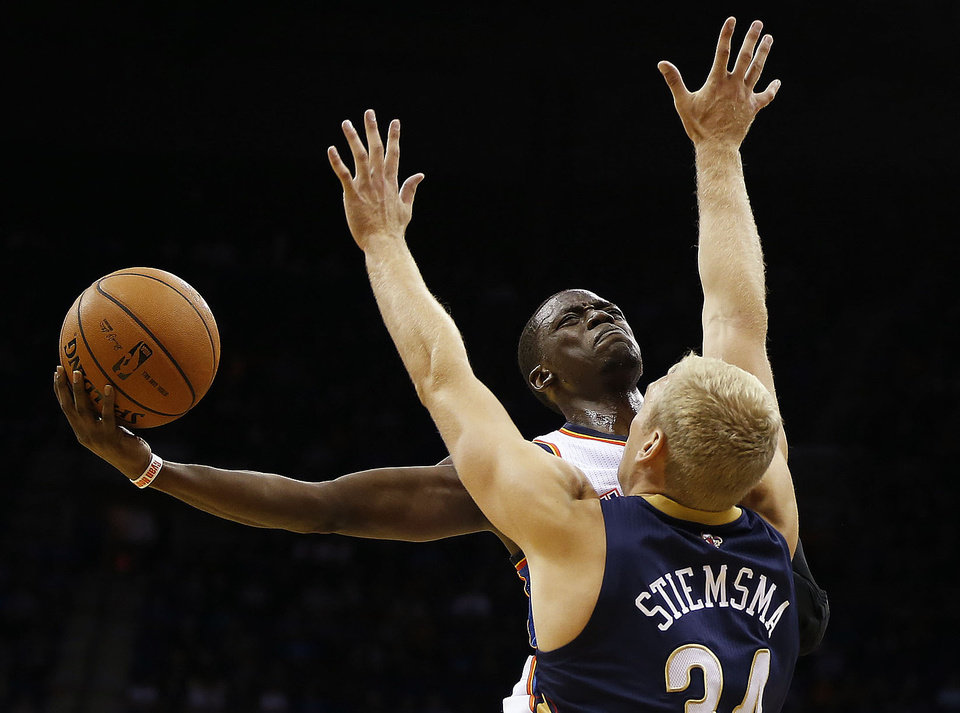 Photo - OKC's Reggie Jackson soars toward the basket against New Orleans' Greg Stiemsma, during the OKC Thunder-New Orleans Pelicans preseason basketball game, at the BOK Center, on Thursday, Oct. 17, 2013. CORY YOUNG/Tulsa World ORG XMIT: DTI1310172137492793