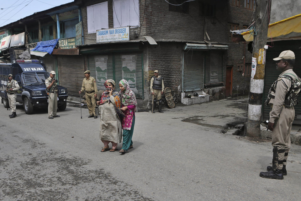 Photo - Kashmiri Muslim women walk past Indian paramilitary soldiers as they stand guard in Srinagar, India, Friday, July 4, 2014. Shops, businesses and schools are shut in Indian-controlled Kashmir after separatist groups opposed to Indian rule announced a strike to protest a visit by the country's Prime Minister Narendra Modi. Modi is on his first official visit to the disputed Himalayan region and is expected to inaugurate a railway line and a power station, and also review security and development. (AP Photo/Dar Yasin)