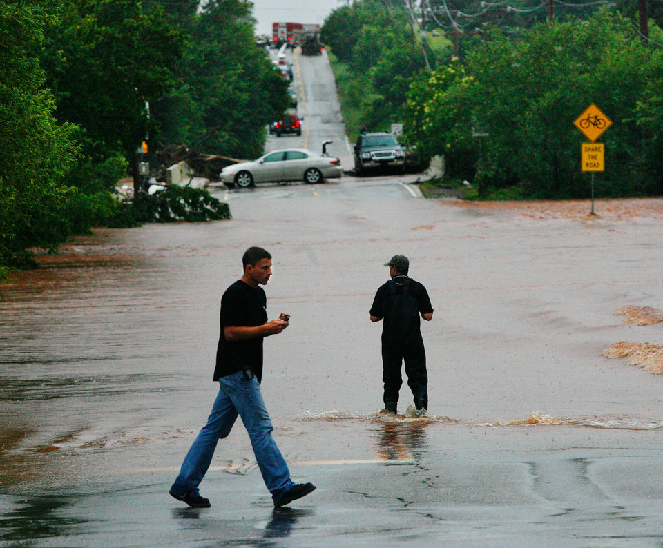 Photo - Two men walk into the rising water, west of Sooner Road on Hefner. Cars are stranded on a bridge in background. Firefighters made several swift-water rescues in this area Monday. Torrential rain caused flooding in Oklahoma City, Monday, June 14, 2010.     by Jim Beckel, The Oklahoman