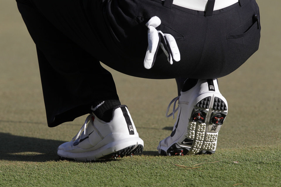 Photo -   CORRECTS TO CHANGING SHOES ON THE SIXTH HOLE AND DROPS HEEL PAIN - Detail of Tiger Woods Nike shoes during the second round of the Players Championship golf tournament at TPC Sawgrass, Friday, May 11, 2012, in Ponte Vedra Beach, Fla. Woods changed his shoes during the sixth hole. (AP Photo/John Raoux)
