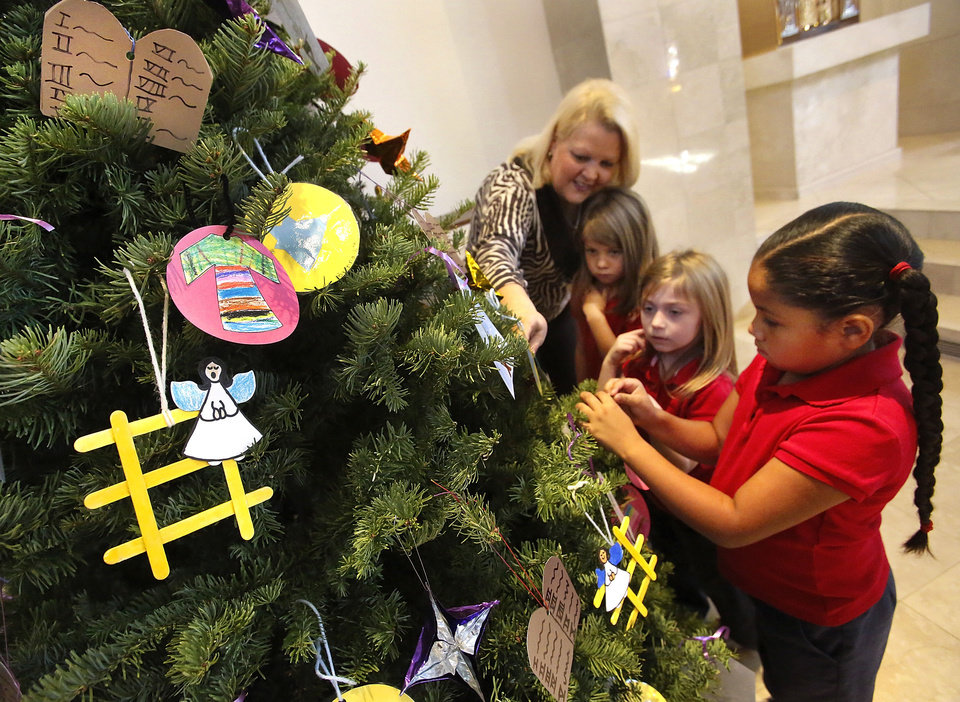 Photo - Foreground to background, kindergarten students Syanne McKaufman, Camryn Rodriquez-Stone, Avery O'Neal and St. James Catholic Principal Anne Codding decorate the school's Jesse tree displayed near the altar at St. James the Greater Catholic Church. Photos by Jim Beckel, THE OKLAHOMAN