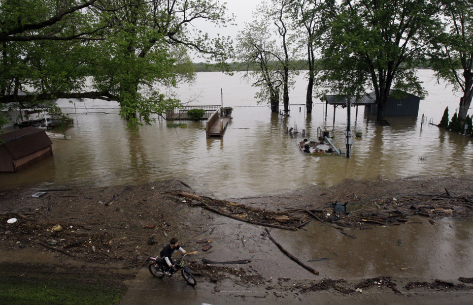 Photo - A young boy rides his bike around debris and floodwaters in Utica, Ind., Wednesday, April 27, 2011. (AP Photo/Darron Cummings)