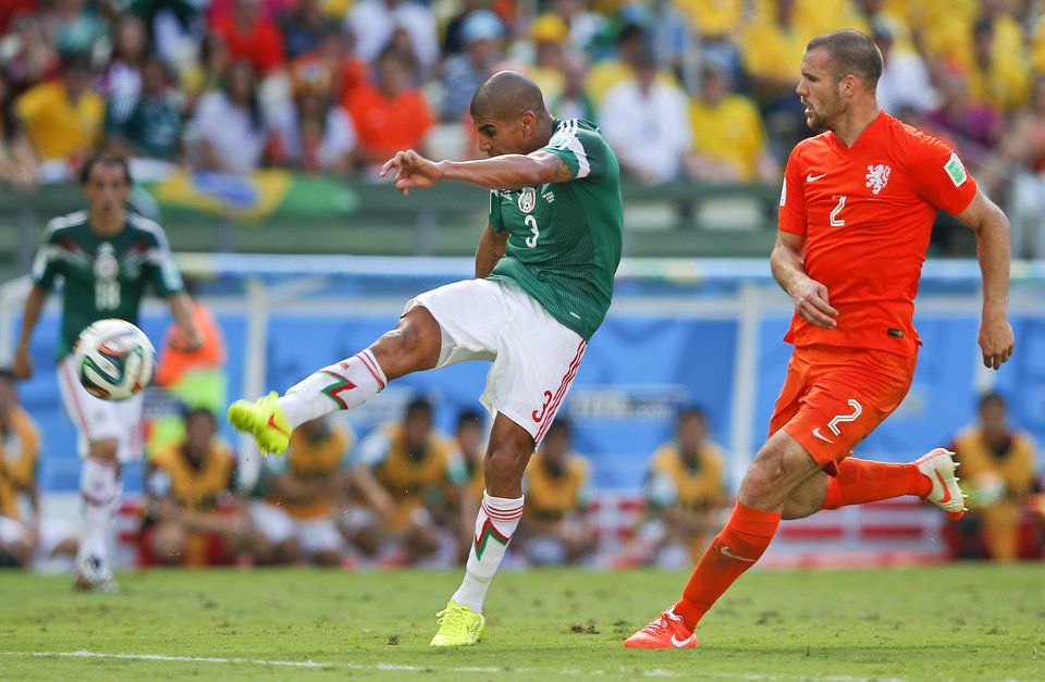 Photo - Netherlands' Ron Vlaar keeps an eye on Mexico's Carlos Salcido as he takes a shot on goal during the World Cup round of 16 soccer match between the Netherlands and Mexico at the Arena Castelao in Fortaleza, Brazil, Sunday, June 29, 2014. (AP Photo/Eduardo Verdugo)