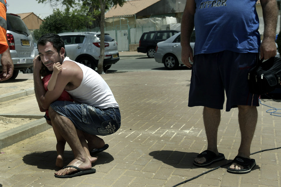 Photo - An Israeli hugs his child outside  a shelter as a siren warning of incoming rockets is heard around the southern city of Beersheba, Israel, Saturday, July 12, 2014. Israeli airstrikes overnight targeting Hamas in Gaza hit a mosque its military says concealed the militant group's weapons, in an offensive that showed no signs of slowing down. Israel launched its campaign five days ago to stop relentless rocket fire on its citizens. While there have been no fatalities in Israel, Palestinian officials said overnight attacks raised the death toll there to over 120, with more than 920 wounded. (AP Photo/Tsafrir