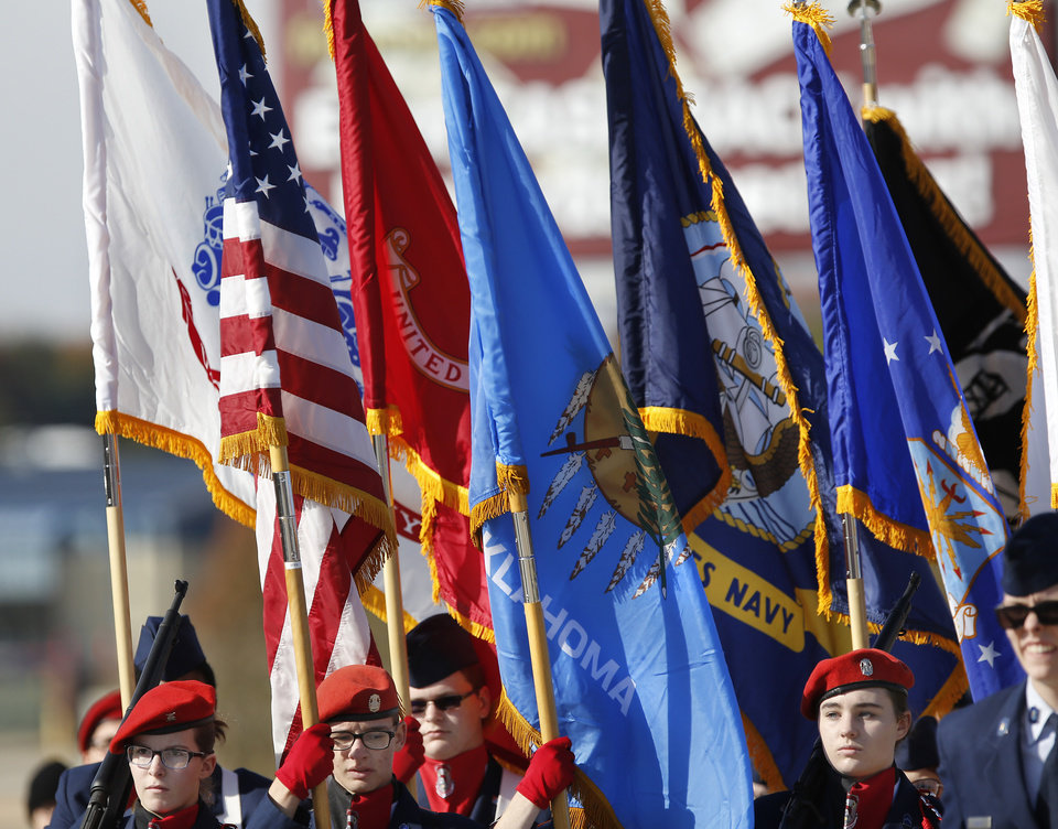 Photo - Members of  Carl Albert High School's Air Force JROTC unit carry flags in the Midwest City Veteran's Day Parade on Friday, Nov. 10, 2017. Photo by Jim Beckel, The Oklahoman