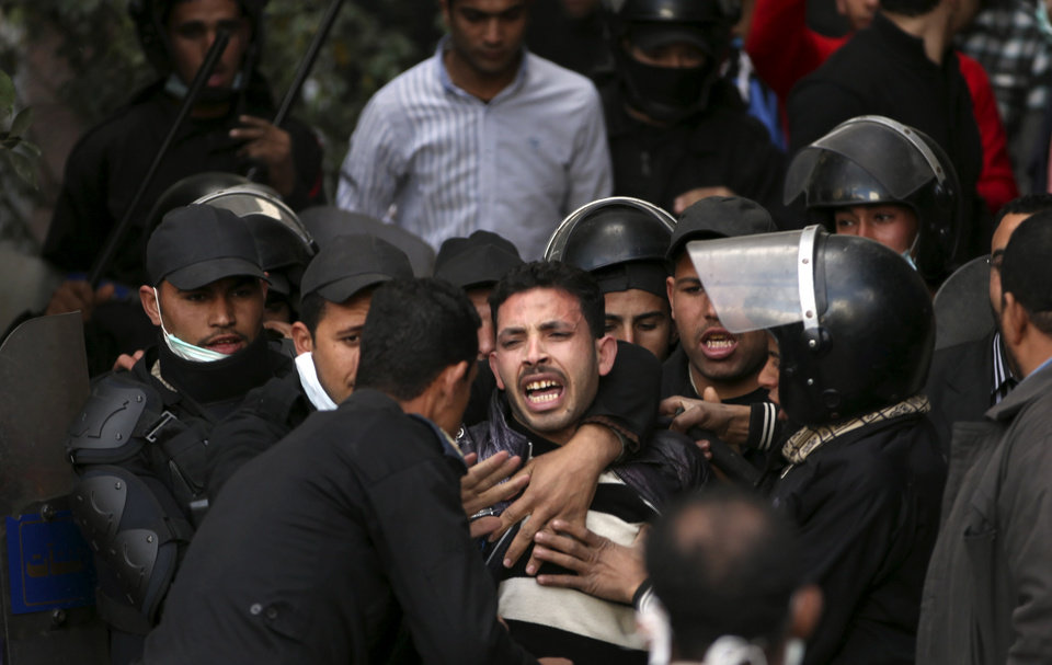 Photo - FILE - In this Wednesday, Jan. 30, 2013 file photo, Egyptian riot police arrest a man during clashes with protesters near Tahrir Square in Cairo, Egypt. With near impunity and the backing of the Islamist president, Egyptian police have over the past week used excessive and often deadly force against protesters across much of the country, regaining their Mubarak-era notoriety as a tool of repression. With nearly 60 people dead and hundreds injured, police have re-emerged as a significant political player after spending the past two years on the sidelines. (AP Photo/Khalil Hamra, File)