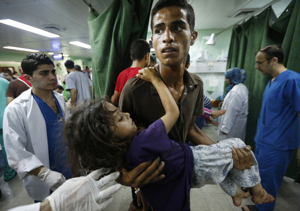 Photo - A Palestinian youth carries a child, wounded in an Israeli strike on a compound housing a U.N. school in Beit Hanoun, in the northern Gaza Strip, into the emergency room of the Kamal Adwan hospital in Beit Lahiya, Thursday, July 24, 2014. Israeli tank shells hit the compound, killing more than a dozen people and wounding dozens more who were seeking shelter from fierce clashes on the streets outside. Gaza health official Ashraf al-Kidra says the dead and injured in the school compound were among hundreds of people seeking shelter from heavy fighting in the area. (AP Photo/Lefteris Pitarakis)