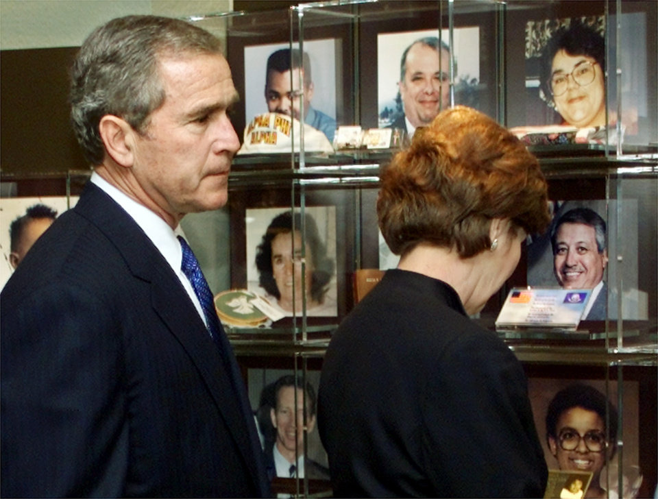 Photo - President George W. Bush and first lady Laura Bush view photos of victims of the Oklahoma City bombing as they attend the dedication of a museum at the Oklahoma City National Memorial Center on Monday, Feb. 19, 2001. (AP Photo/J. Scott Applewhite)