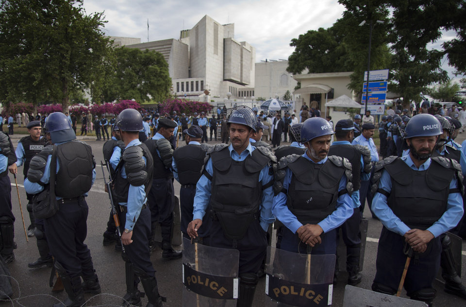 Photo -   Policemen in riot-gears cordon off the Supreme court as Pakistani Prime Minister Yousuf Raza Gilani, not seen, appears for a hearing in Islamabad, Pakistan, Thursday, April 26, 2012. The Supreme Court convicted Gilani of contempt on Thursday for refusing to reopen an old corruption case against President Asif Ali Zardari on Thursday, but spared him a prison term in a case that has stoked political tensions in the country. (AP Photo/B.K. Bangash)