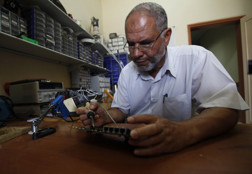 Photo - In this Monday, June 24, 2013 photo, Nabhan Rantisi, 58, fixes an electronic device at his workshop at Al-Aqsa college in Gaza City. On the day of his induction, Baraa Rantisi, Nabhan's nephew, was told to wait near a mosque. A white car drove up. Secret passwords were exchanged. And then he was sworn into the Muslim Brotherhood, an exclusive movement that sees itself on a divine mission to establish Islamic rule. AP reporters got rare access to the Rantisi family, the closest thing to a royal clan in the Brotherhood in Gaza, at a time when the movement is under siege throughout the region. (AP Photo/Hatem Moussa)