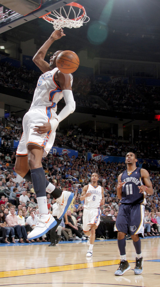 Oklahoma City\'s Kevin Durant dunks the ball as Mike Conley of Memphis watches during the NBA basketball game between the Oklahoma City Thunder and the Memphis Grizzlies at the Ford Center in Oklahoma City on Wednesday, April 14, 2010. Photo by Bryan Terry, The Oklahoman