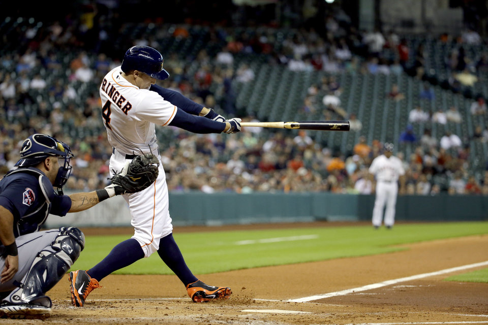 Photo - Houston Astros' George Springer (4) hits a home run as Atlanta Braves catcher Gerald Laird, left, reaches for the pitch during the first inning of a baseball game Tuesday, June 24, 2014, in Houston. (AP Photo/David J. Phillip)