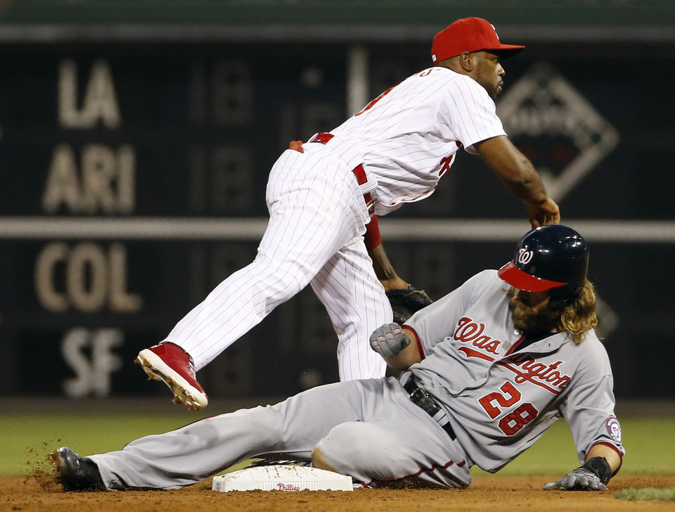 Photo - Washington Nationals' Jayson Werth, bottom, is forced out at second base by Philadelphia Phillies shortstop Jimmy Rollins on a double play hit into by Adam LaRoche during the first inning of a baseball game, Wednesday, Aug. 27, 2014, in Philadelphia. (AP Photo/Matt Slocum)