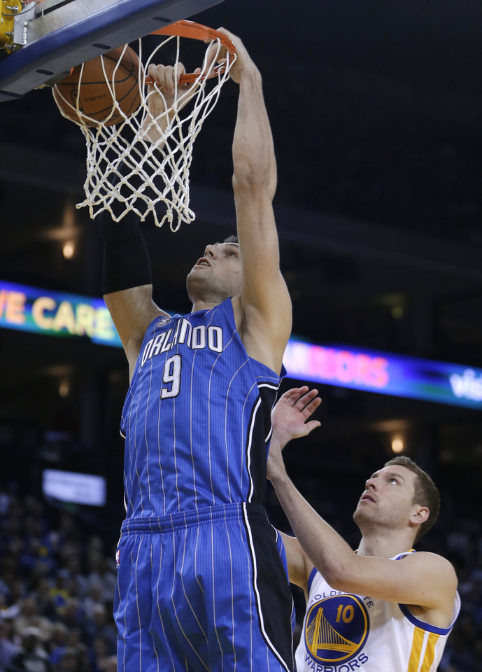 Photo - Orlando Magic center Nikola Vucevic (9) scores over Golden State Warriors' David Lee, right, during the first half of an NBA basketball game Tuesday, March 18, 2014, in Oakland, Calif. (AP Photo/Ben Margot)