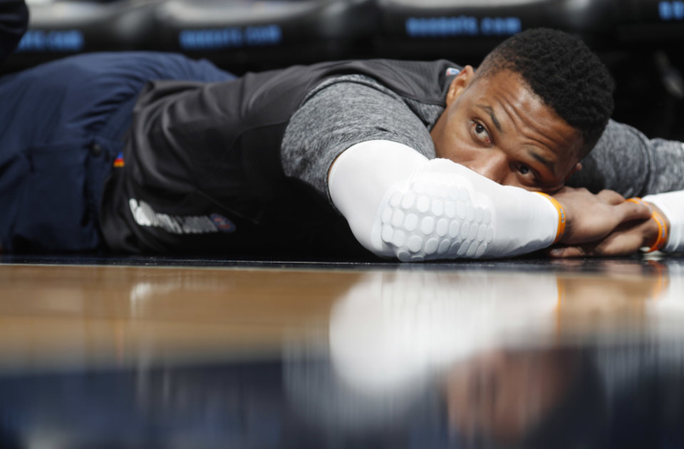 Photo - Oklahoma City Thunder guard Russell Westbrook is reflected on the floor as he is stretched in front of the bench before the team's NBA basketball game against the Denver Nuggets on Thursday, Nov. 9, 2017, in Denver. (AP Photo/David Zalubowski)