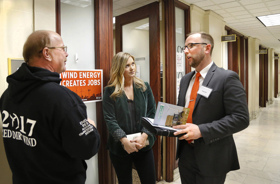 Photo -  From left, Mark McMillin, Destinee Weeks and Heath Herje on Wednesday meet in the hallway outside the Capitol office of Rep. Claudia Griffith. McMillin manages Red Dirt Wind, a wind farm in Hennessey. Weeks is a property owner in Dewey County, and Herje is regional director for Tradewind Energy in Norman. [Photo by Jim Beckel, The Oklahoman]