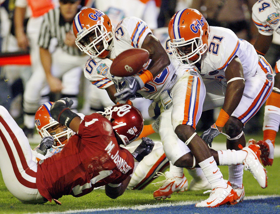 Photo - OU's Manuel Johnson (1) can't pull in a pass late in the second quarter as Florida's Major Wright (21) moves in to intercept the ball with Ahmad Black (35) during the BCS National Championship college football game between the University of Oklahoma Sooners (OU) and the University of Florida Gators (UF) on Thursday, Jan. 8, 2009, at Dolphin Stadium in Miami Gardens, Fla.  PHOTO BY NATE BILLINGS, THE OKLAHOMAN