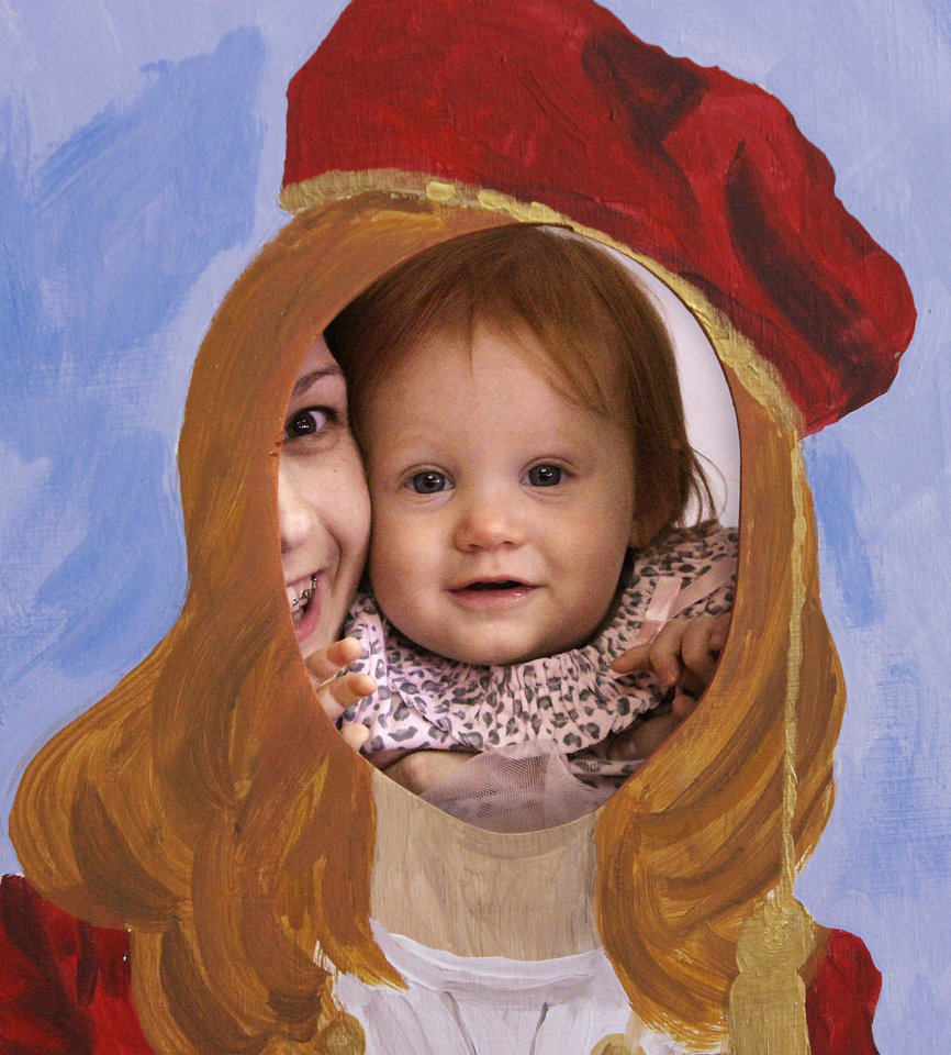 Ella Clair Dunk, age 1, held by her mother, pops her face into a painted cutout featuring a young Greek boy and girl in native dress at St. George Greek Orthodox Church.  Photo by Jim Beckel, The Oklahoman