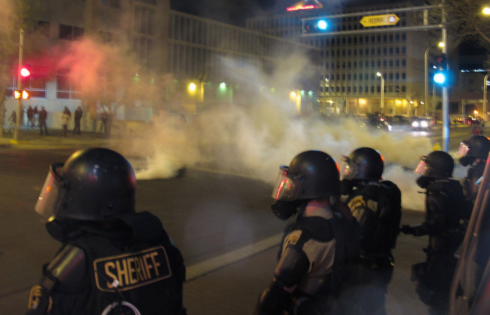 Photo - Riot police launch tear gas toward activists in downtown Albuquerque, N.M. following a 10-hour protest around the city, Sunday, March 30, 2014. Hundreds of protesters marched past riot police in Albuquerque on Sunday, days after a YouTube video emerged threatening retaliation for a recent deadly police shooting. The video, which bore the logo of the computer hacking collective Anonymous, warned of a cyberattack on city websites and called for the protest march. (AP Photo/Russell Contreras)