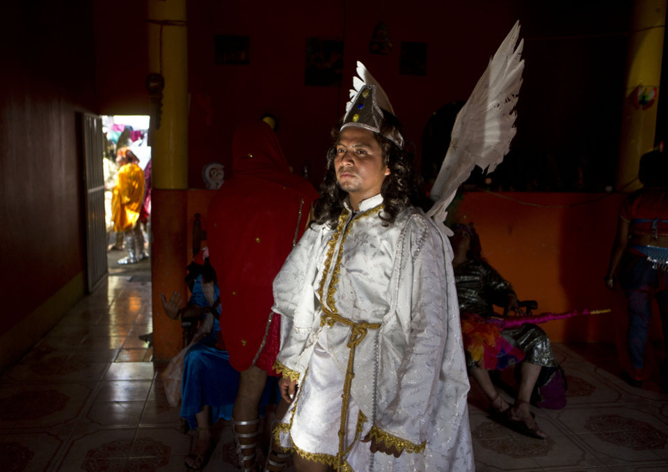 Photo - An actor dressed as a demon from Mount Gethsemane takes a break inside a home as he partakes in the reenactment of Jesus' crucifixion in a